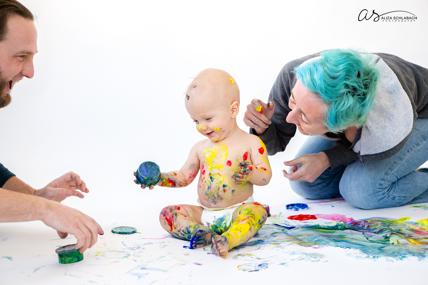 Photo of naked one year old boy and his parents having fun with fingerpaint on a white background