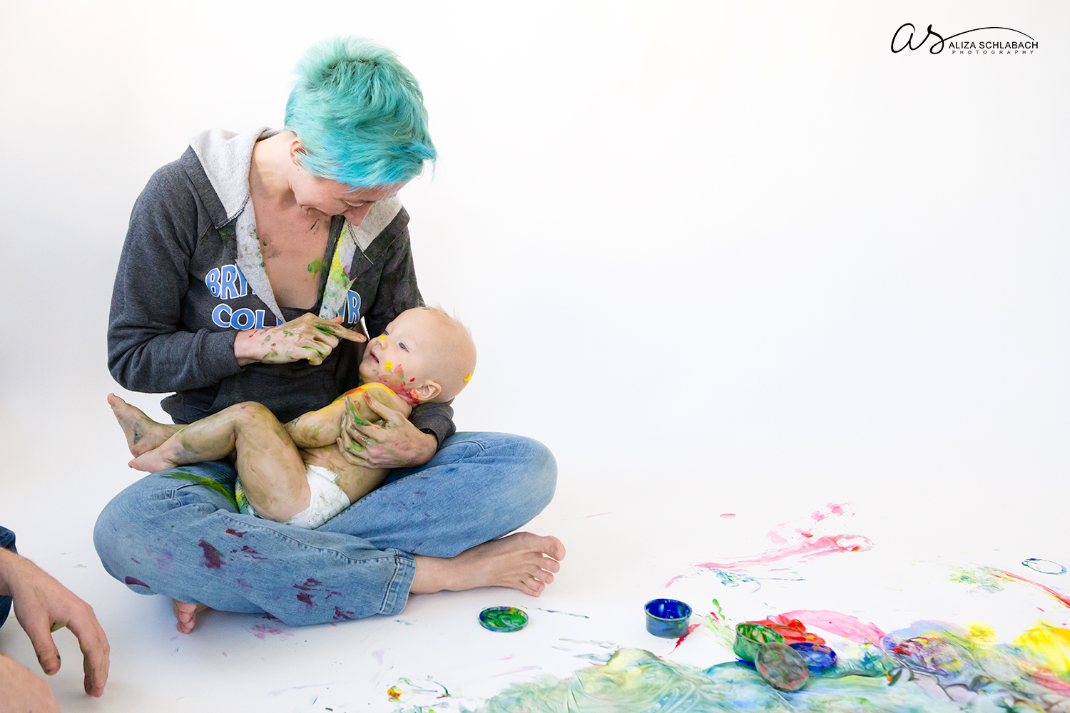 Photo of one year old boy and mother cuddling after messy fingerpainting session