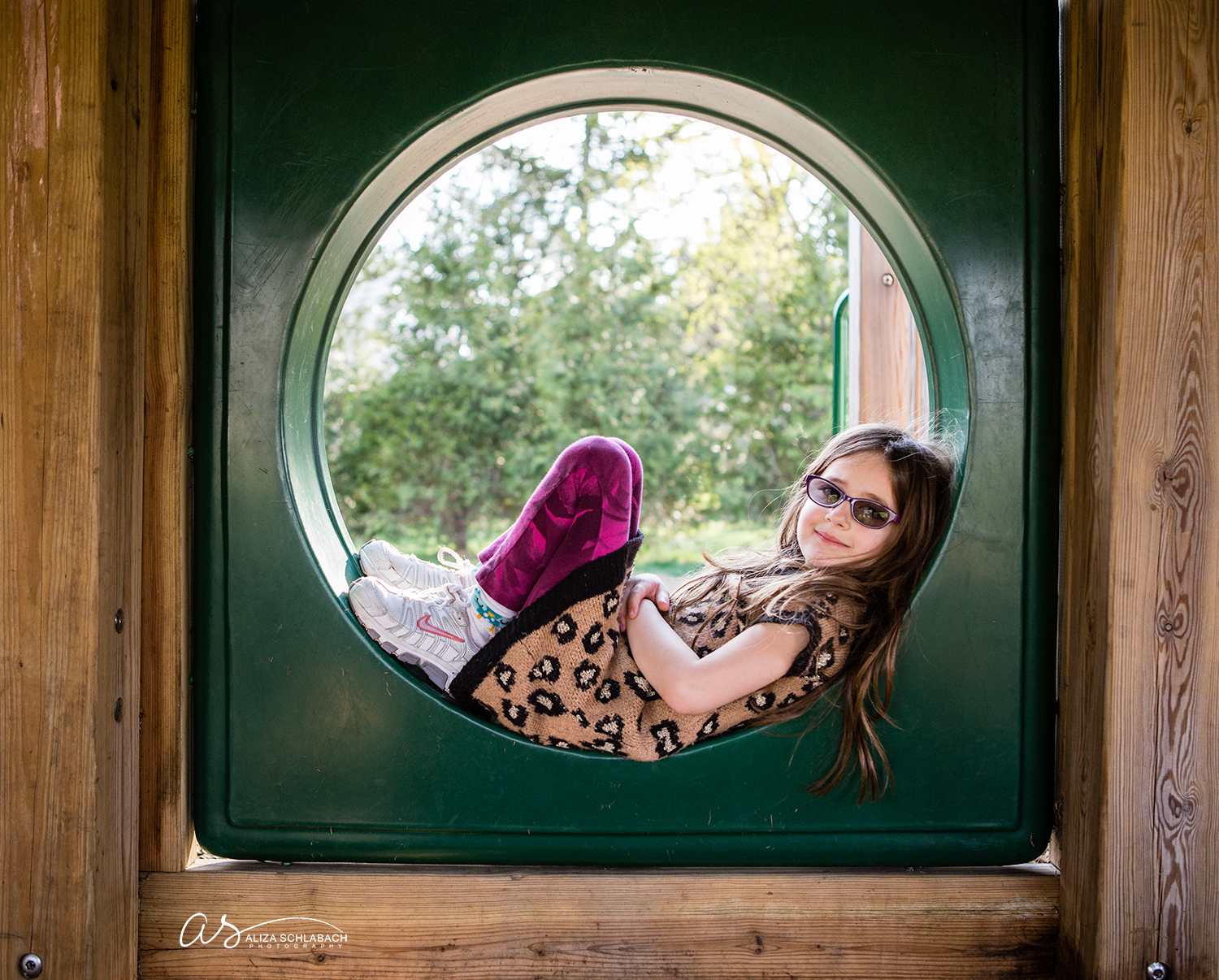 Photo of little girl relaxing in a playground tube
