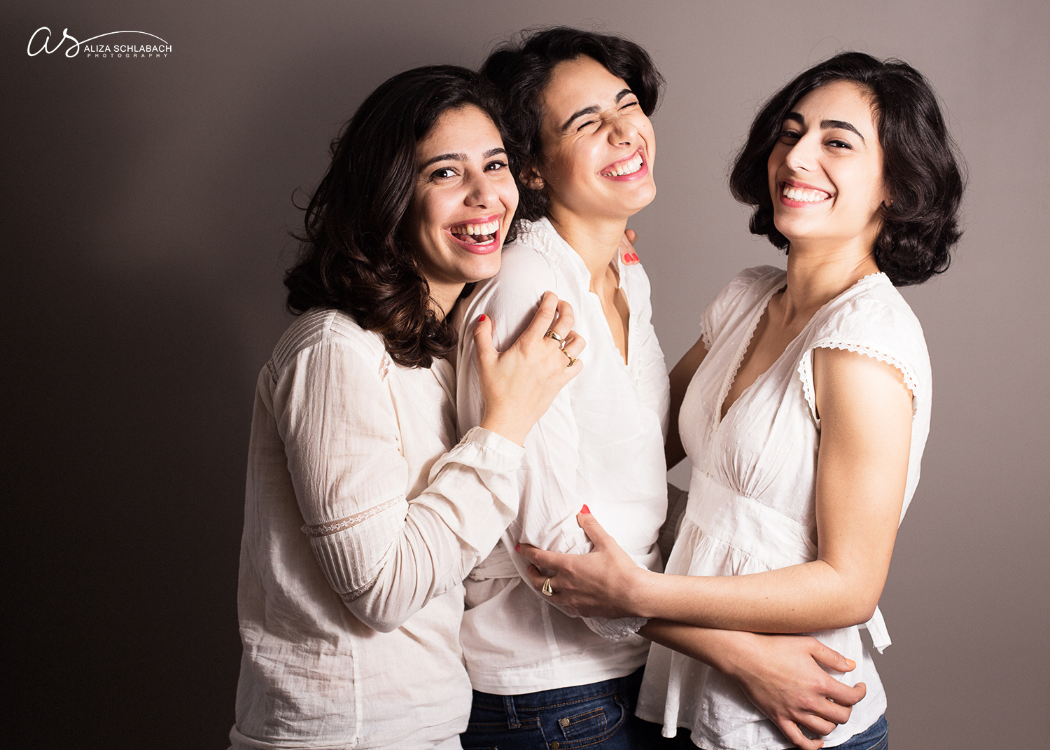 Photograph of three laughing dark haired beauties