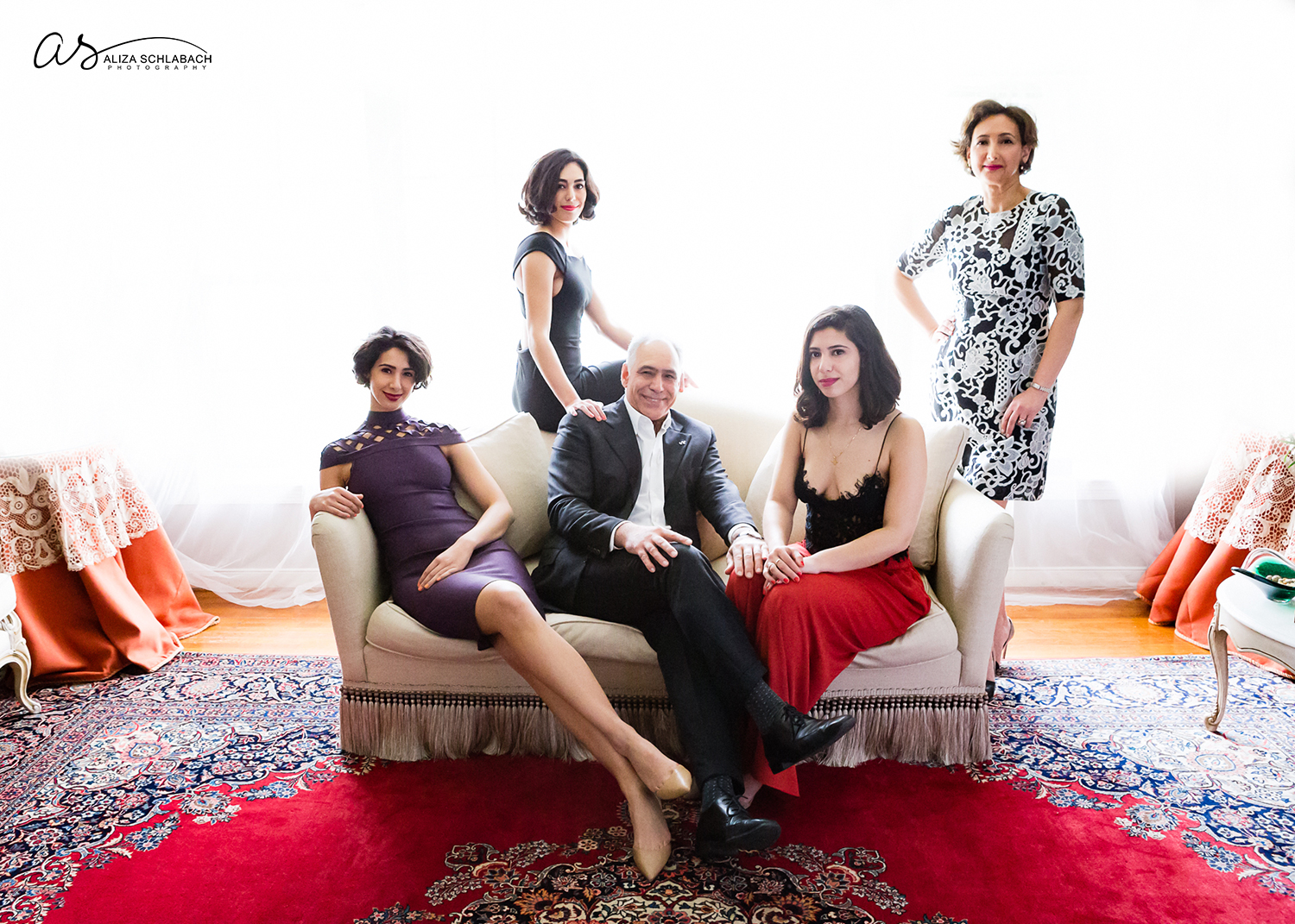 Formal backlit portrait of father, mother, and their three gorgeous grown daughters