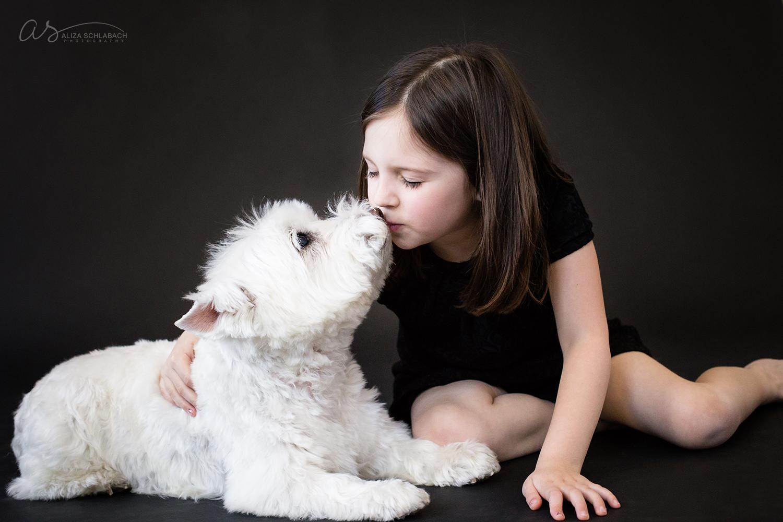 Little girl kissing her white dog