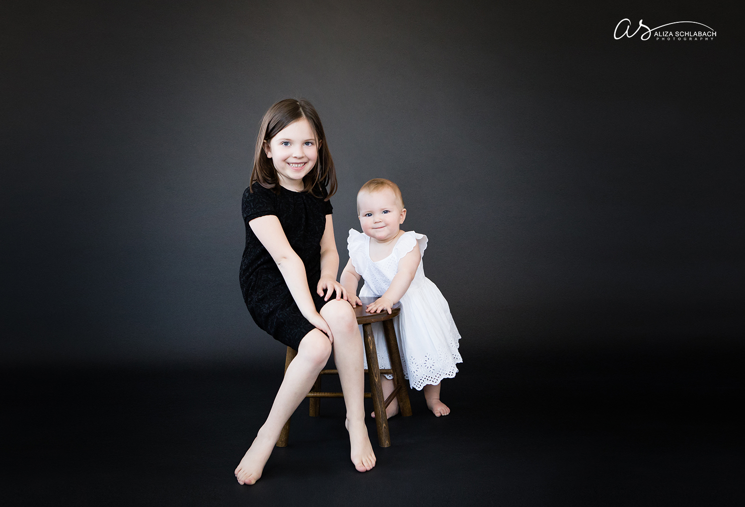 Photo on a black background of 6 and 1 year old sisters