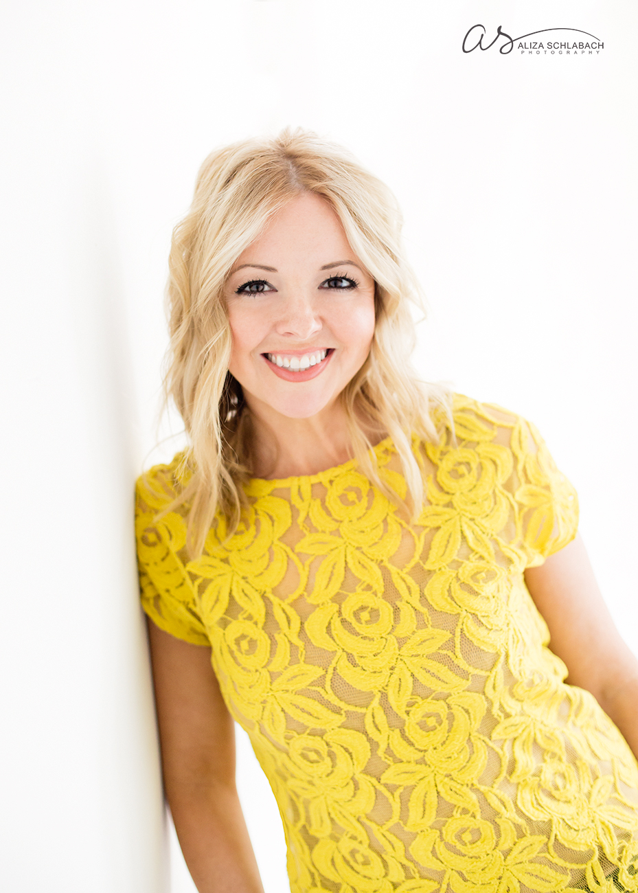 Backlit headshot of pretty blonde woman in a yellow shirt