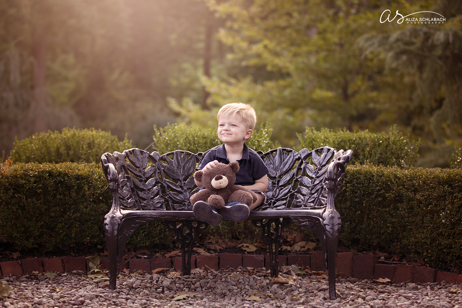 Outdoor portrait of a little blonde boy with his teddy bear on a bench at Appleford Estate in Villanova