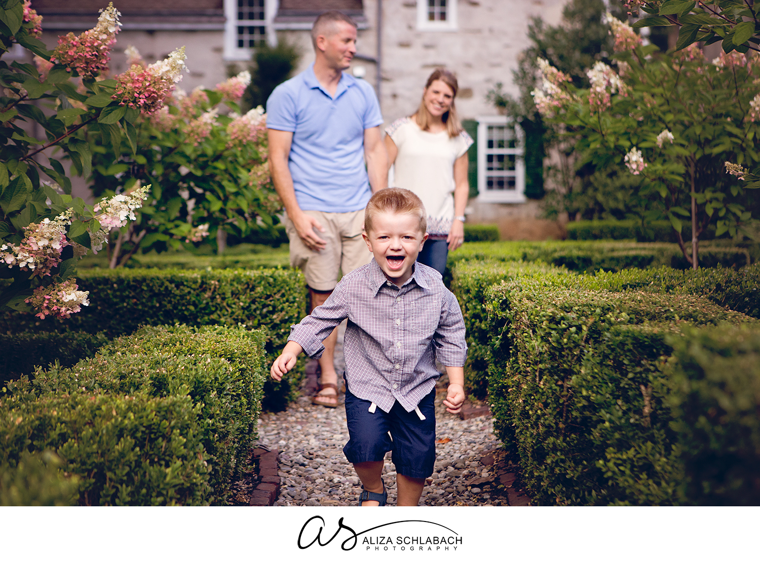 Portrait of parents and laughing toddler running towards camera at Appleford Estate in Villanova on the Main Line