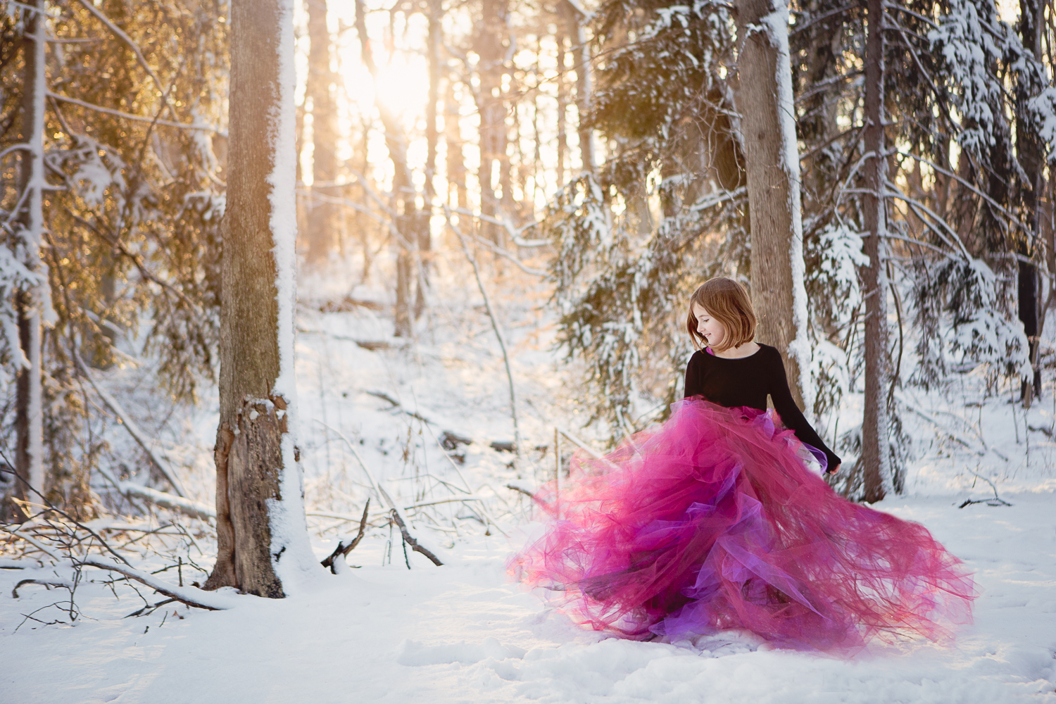 Portrait of a little girl with a fuschia tulle skirt in the snow and forest at sunset -- taken at Haverford College Nature Trail