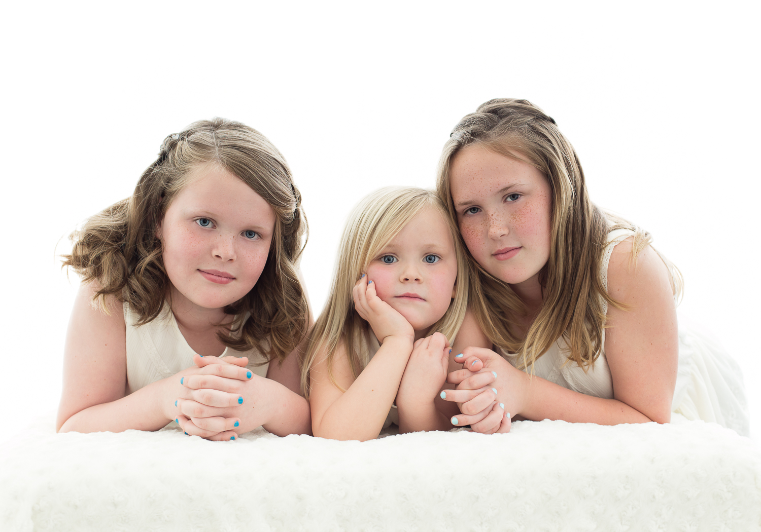 Backlit studio photograph of 3 sisters all in white