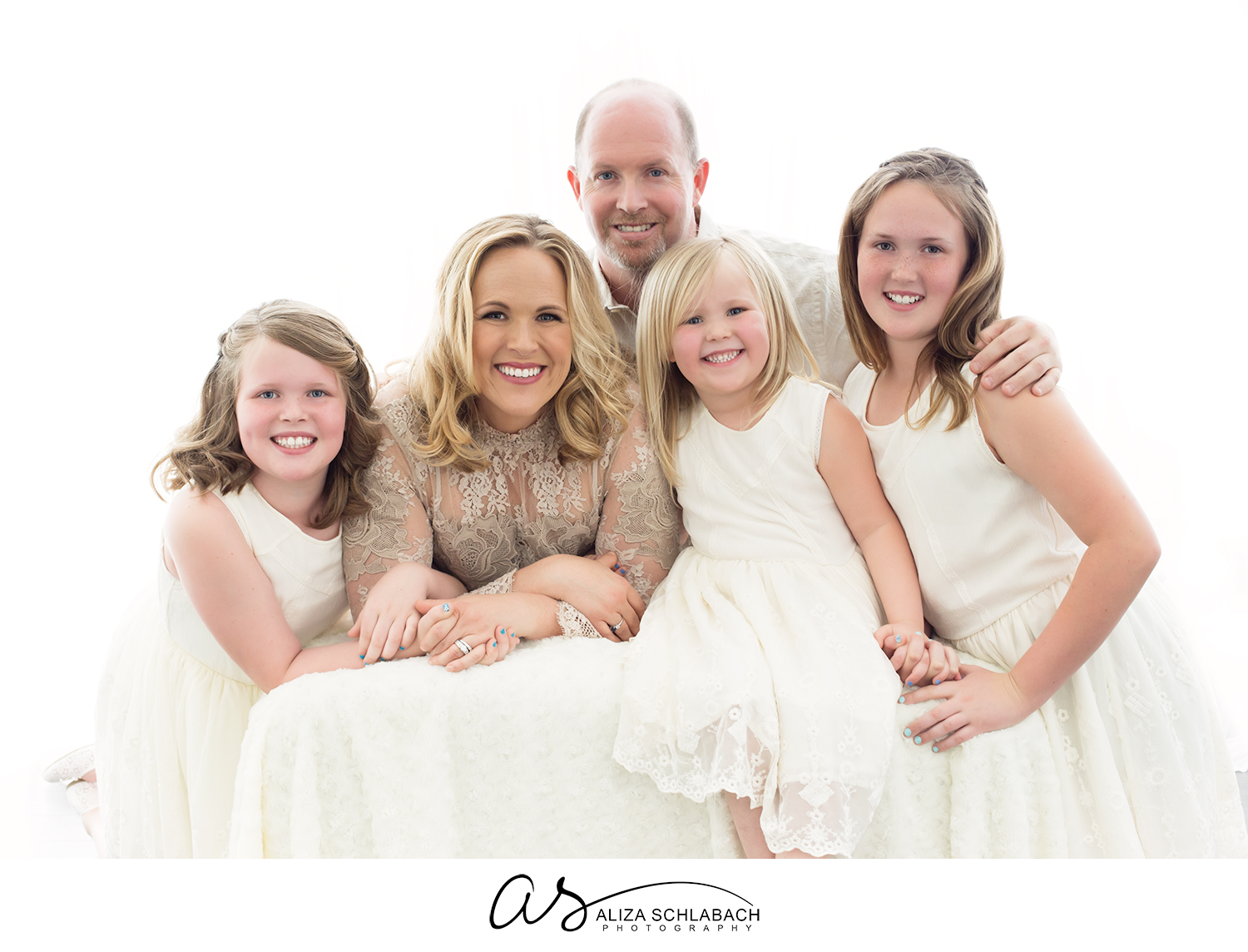 Backlit studio portraiture of a family with three daughters all in white