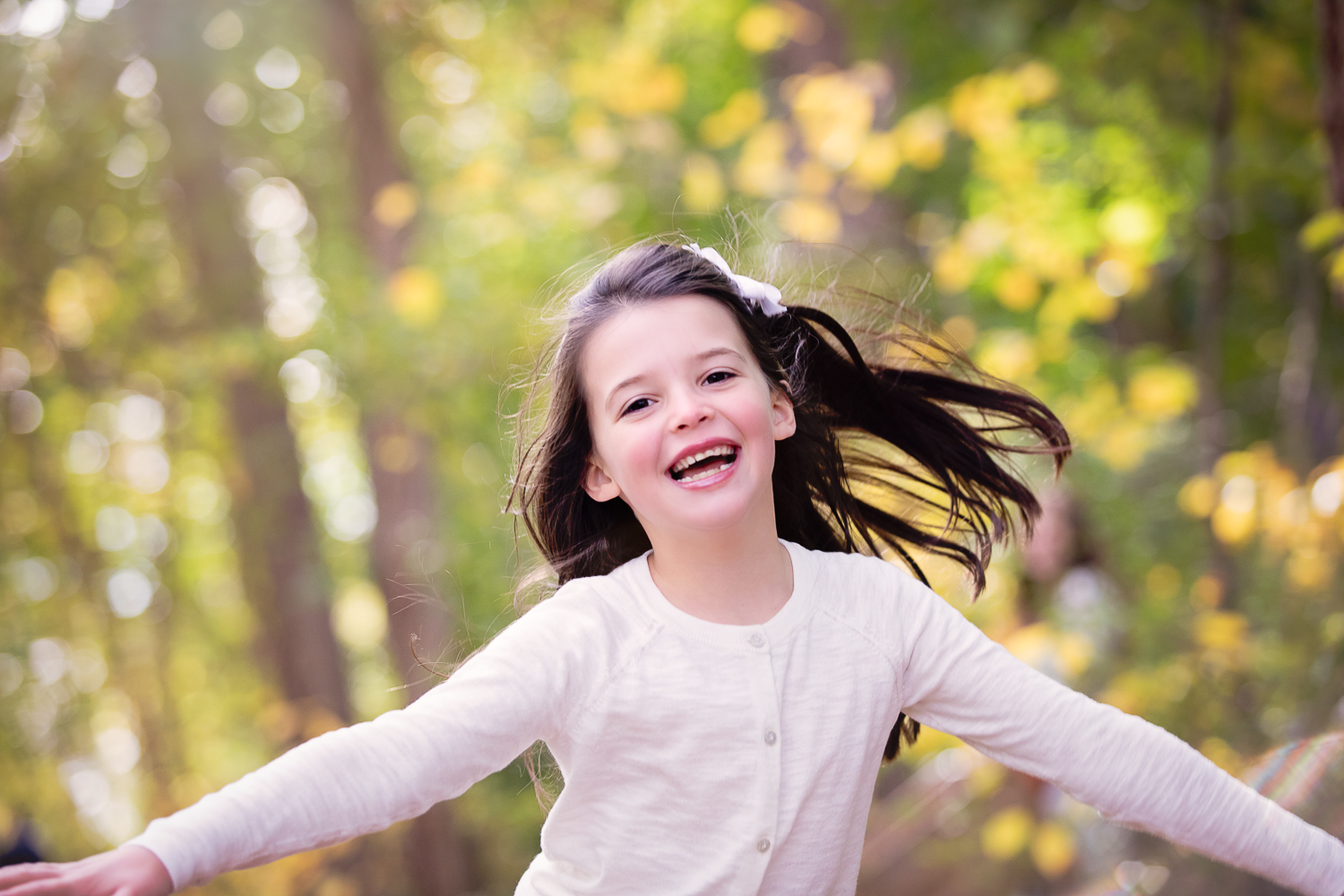 Fall photo of a little girl running and laughing under the trees
