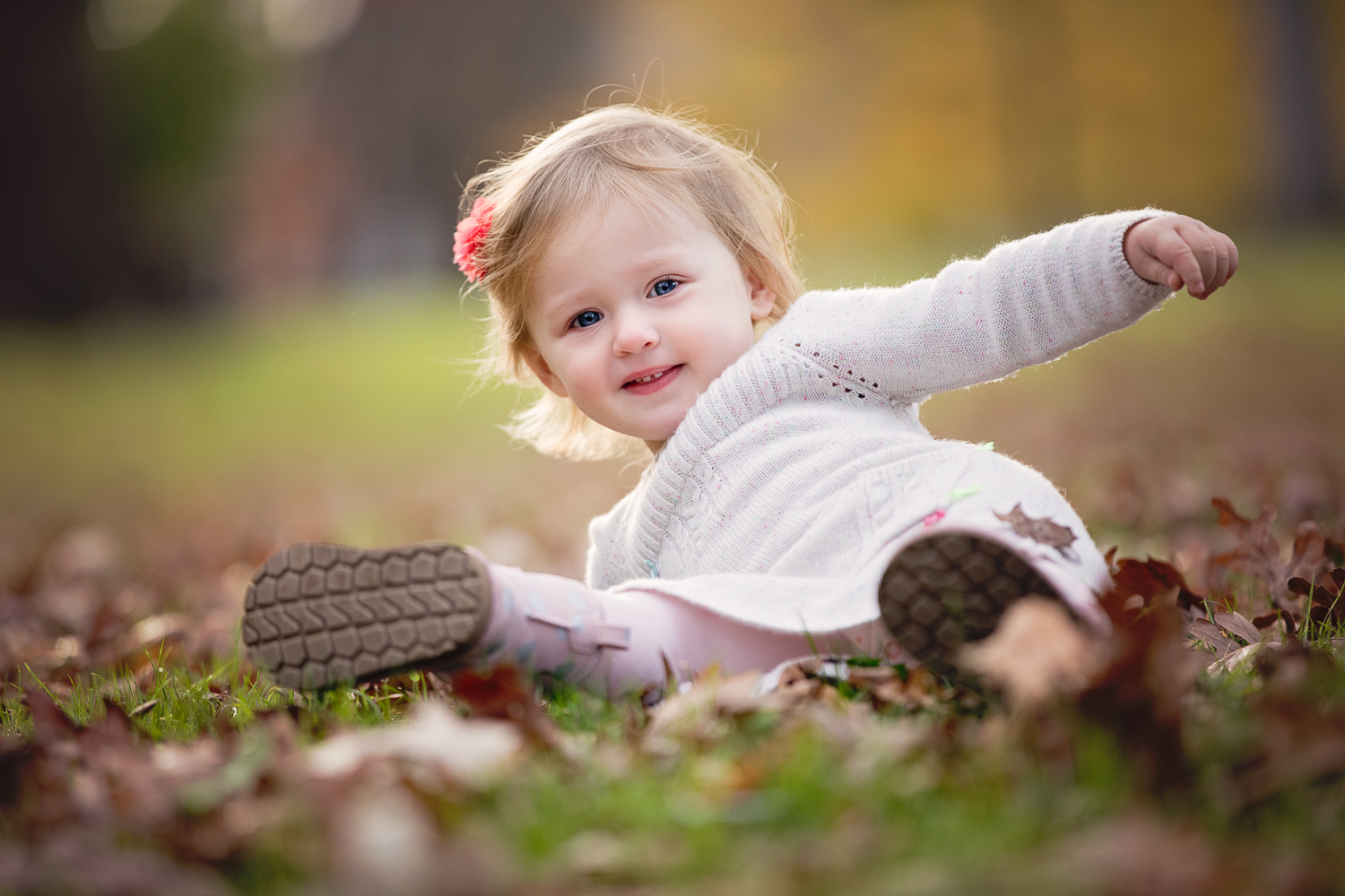 Fall photo of a little girl playing on the ground and falling over