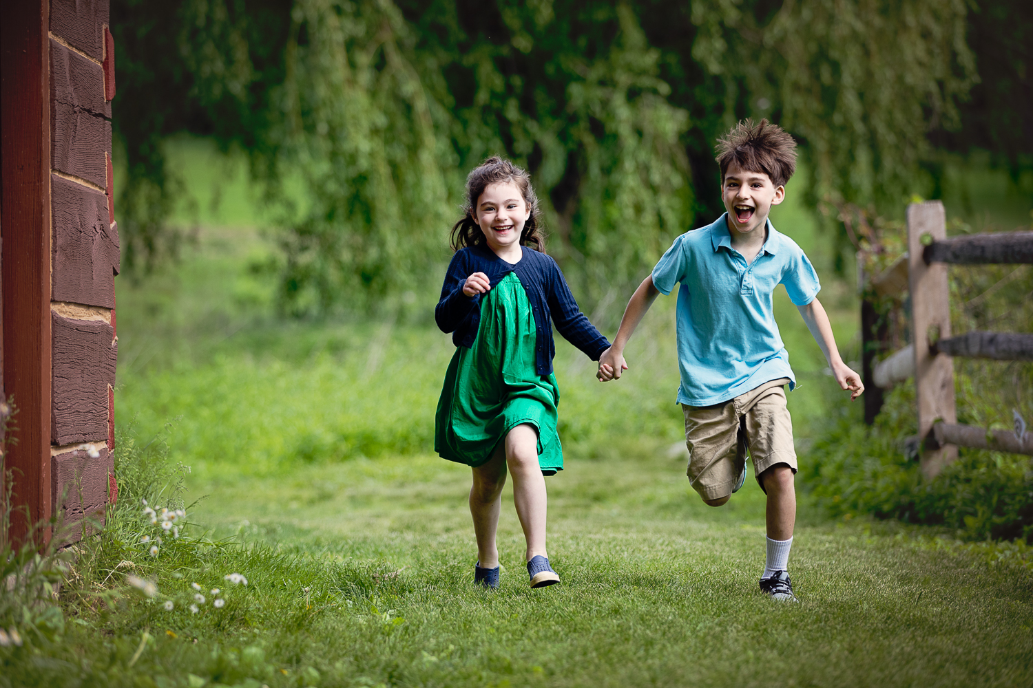 siblings holding hands and running