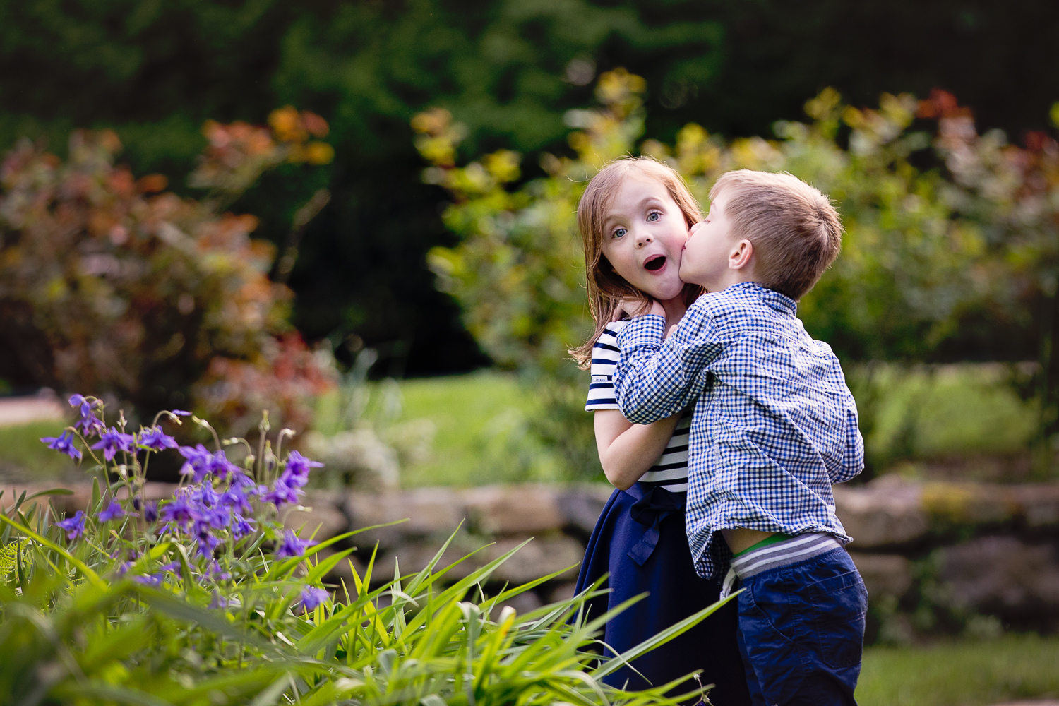 Outdoor photo of a little boy kissing his big sister on the cheek