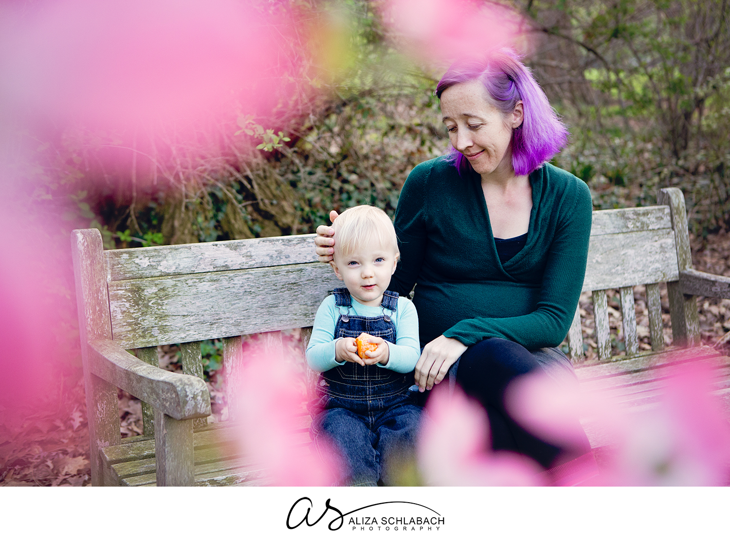 Photo of a mom with purple hair and her cute little boy through the spring blossoms