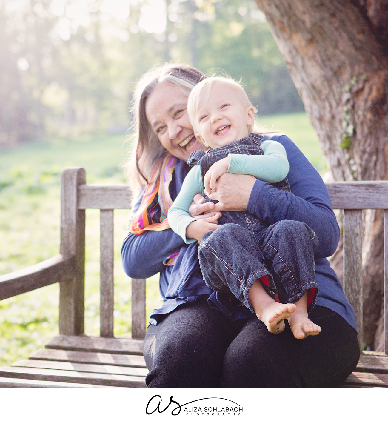 Sundrenched photo of a grandma holding her grandson and laughing on a bench