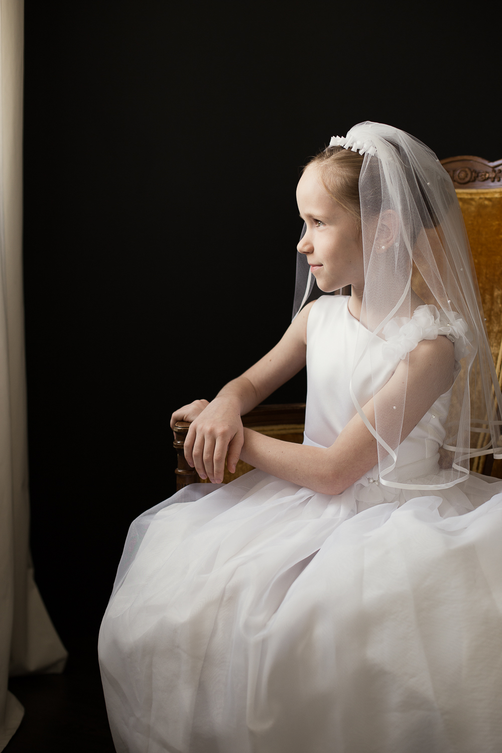 Portrait of a girl in a communion dress and veil by a window in a gold chair