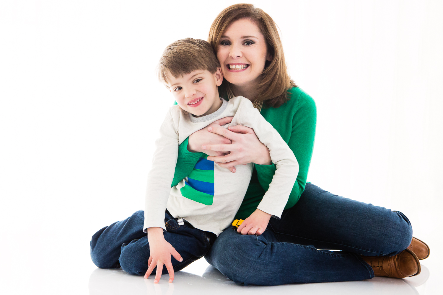 Photograph on white backdrop with an woman and her little boy