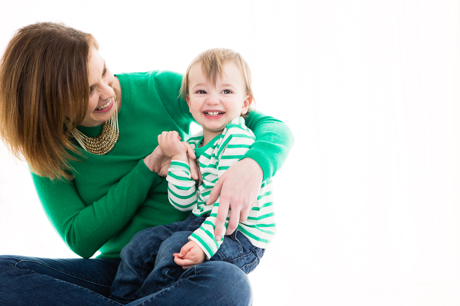 Photo on white backdrop of a woman in green holding a little boy in a green and white striped shirt