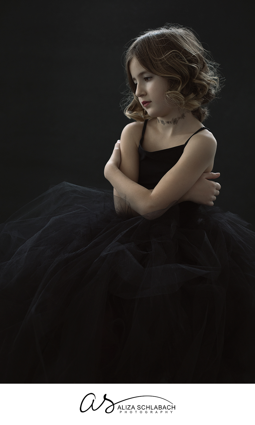 Portrait of a serious eight year old girl in a black tulle skirt with beautiful lighting