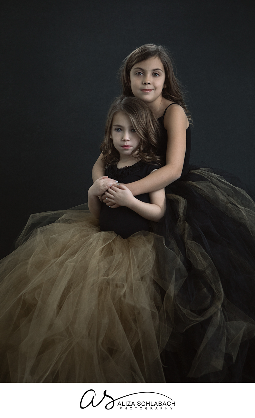 Studio portrait photography of little sisters in black and gold tulle skirts