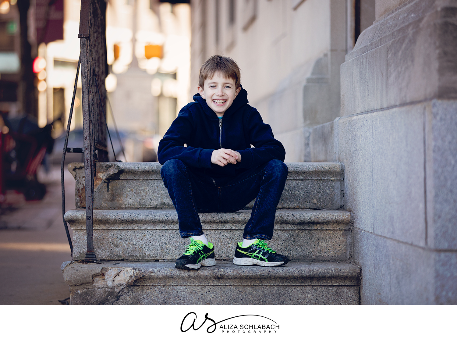 Outdoor photo of a boy laughing on some stone steps