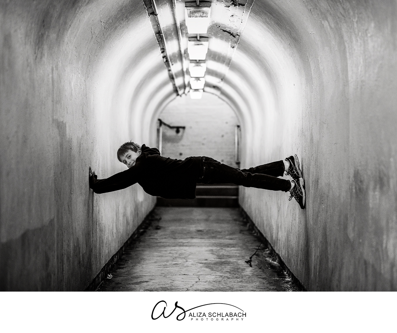 Photo of a boy doing stunts in a train tunnel