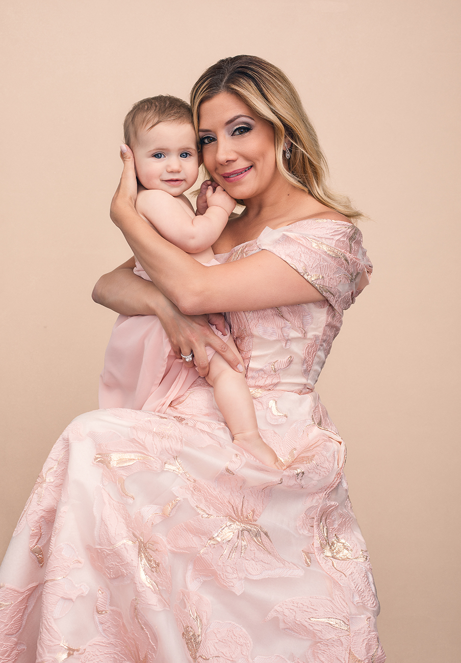 Portrait of a mother in a pink gown holding her baby daughter