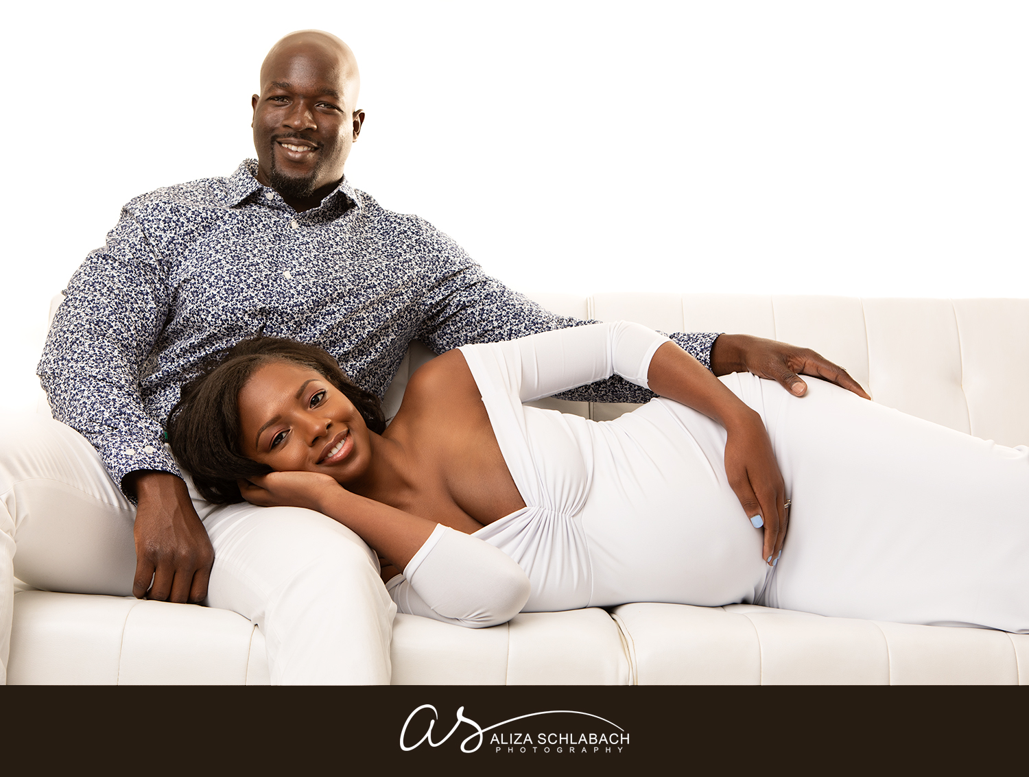 Backlit photo of a black pregnant woman in a white dress with her handsome husband