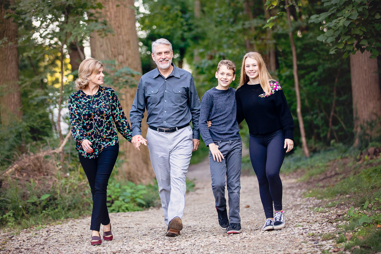 Photograph of a happy family of four walking on the Haverford College Nature Trail