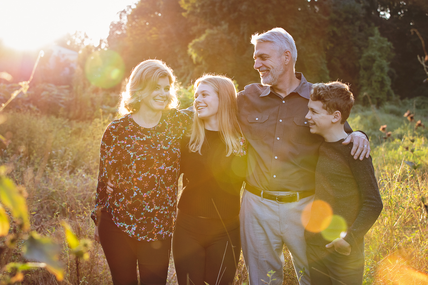 Photograph of a family of four with intense sun flare at golden hour