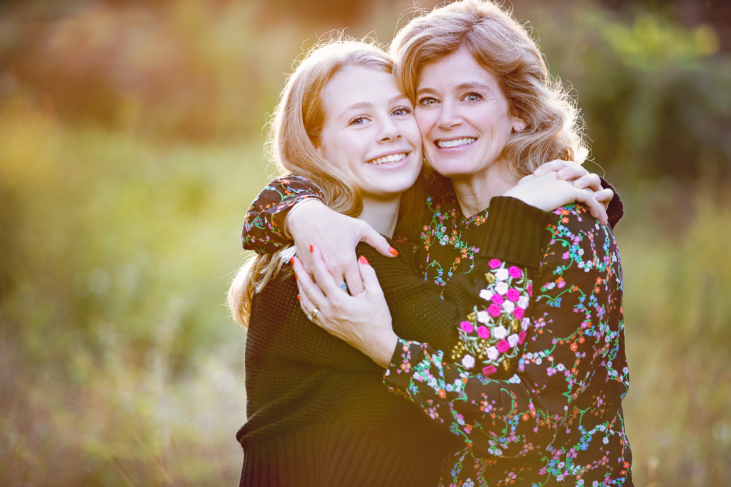 Golden hour portrait of a mom and her teenage daughter hugging