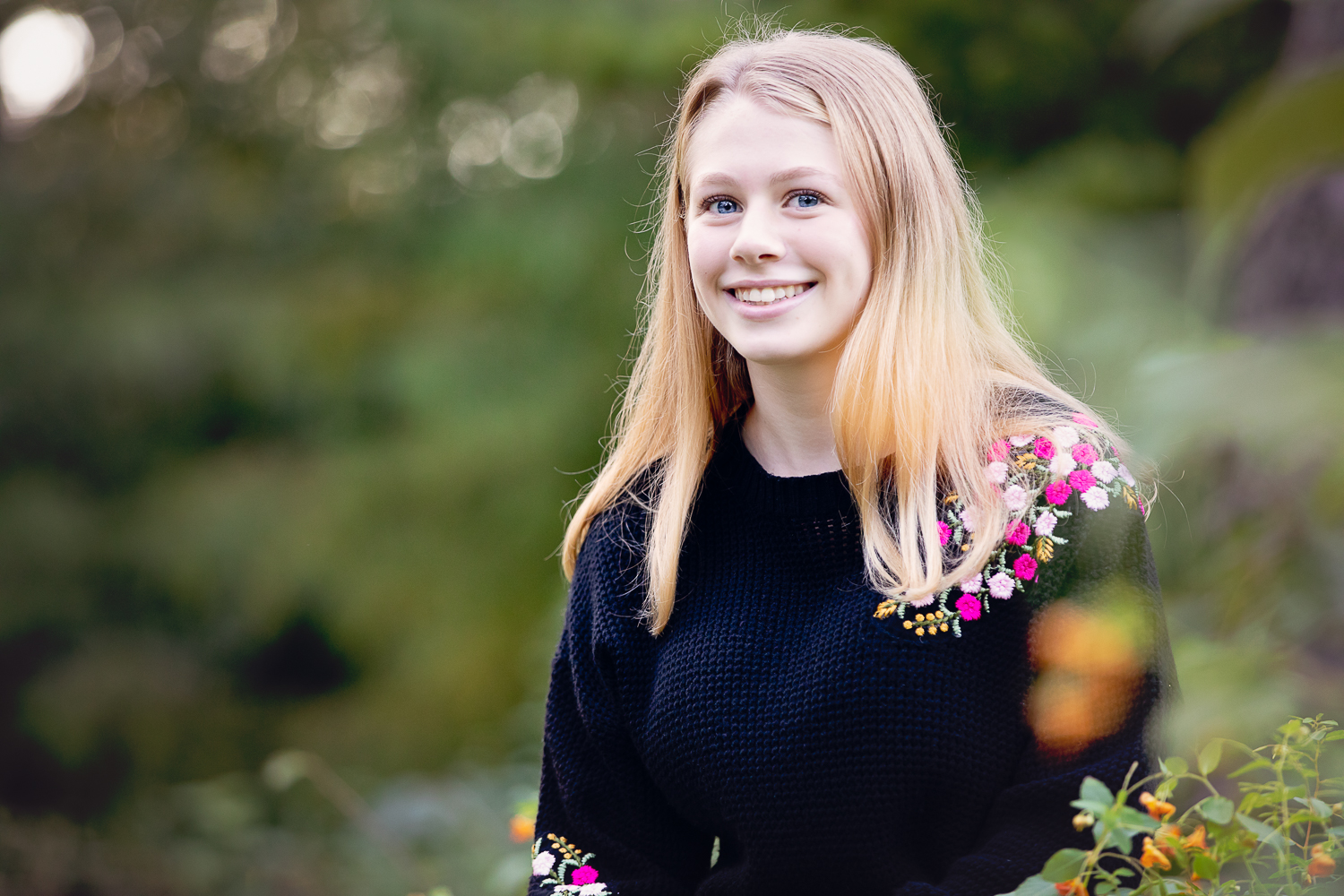 Outdoor photo of a teenage girl in a black sweater