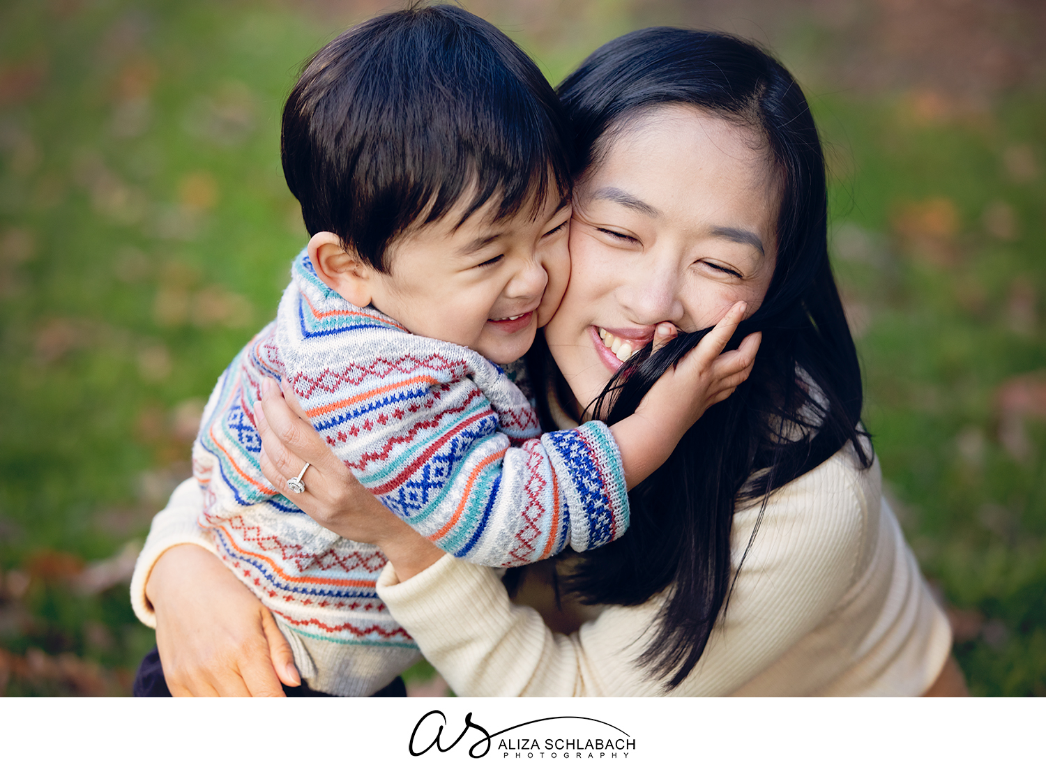 Outdoor photo of an adorable little boy embracing his mother's face. Super cute Japanese family.