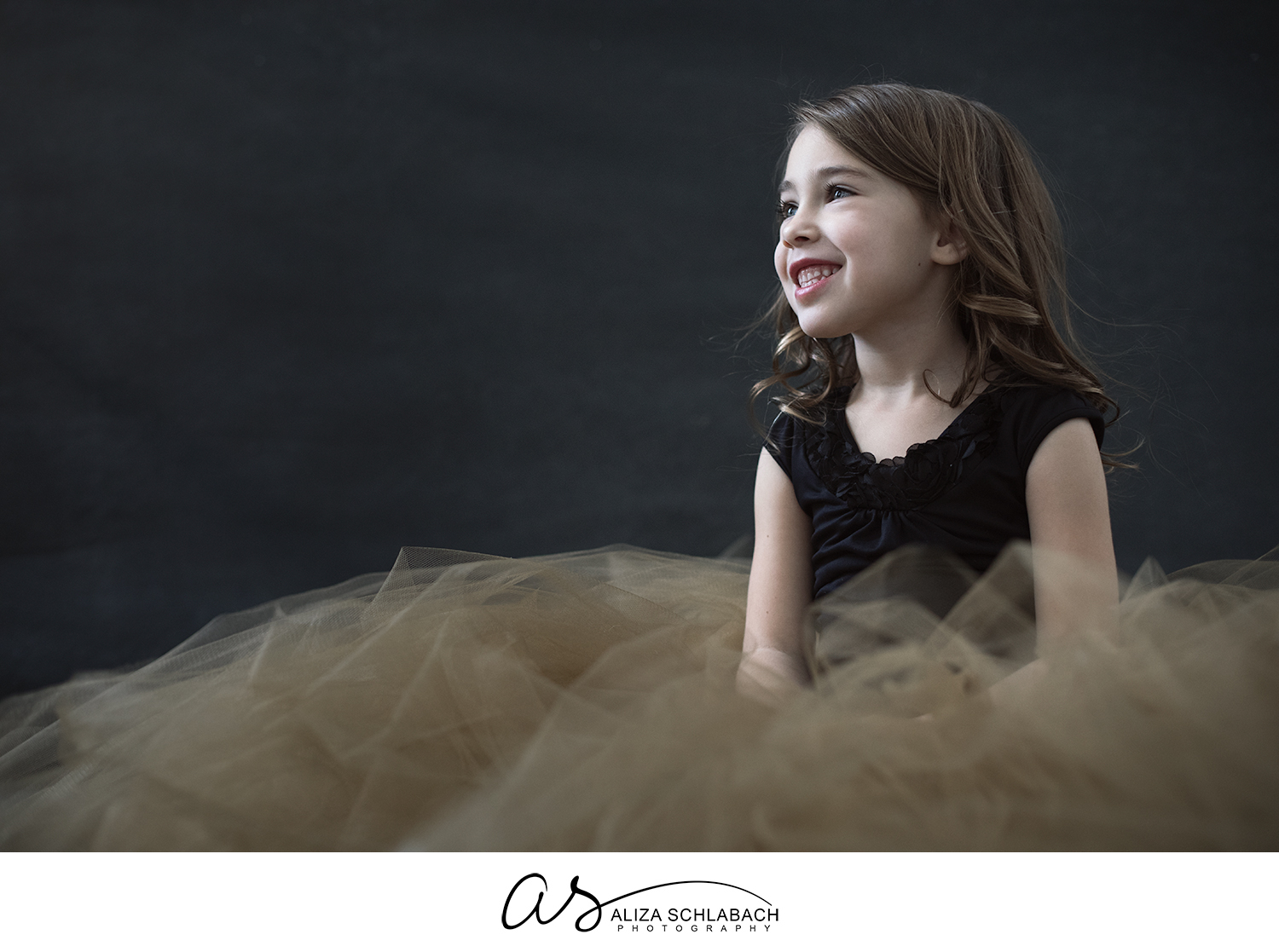 Portrait of a smiling little girl sitting in a gold tulle skirt