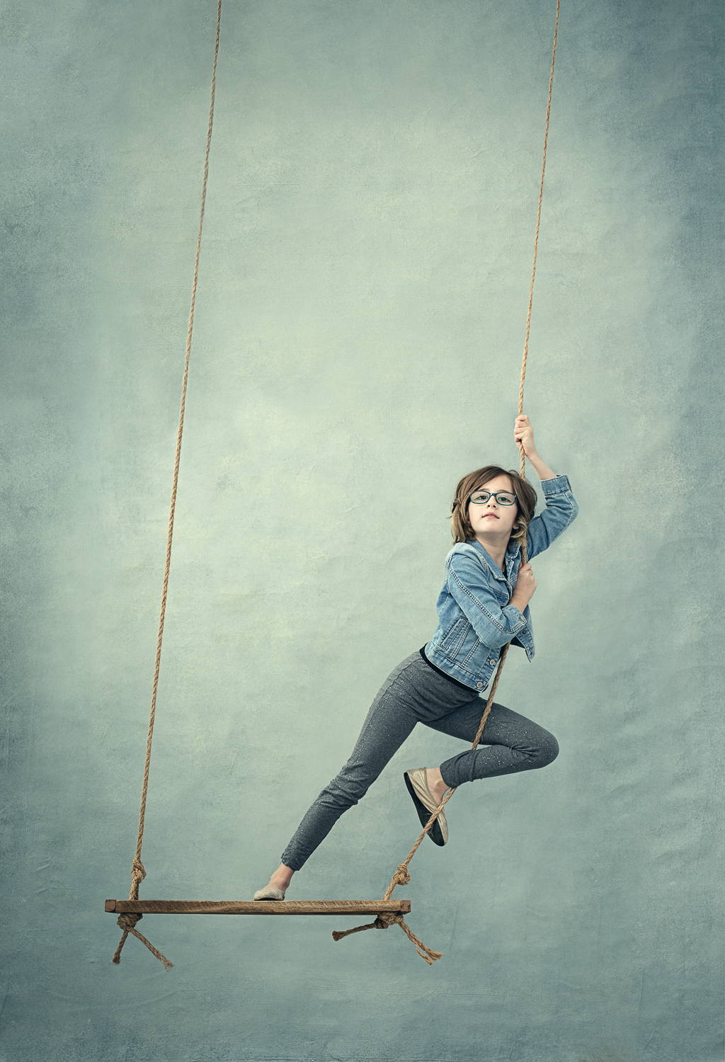 Fine art portrait of a little girl on a wooden swing in front of a hand painted canvas backdrop