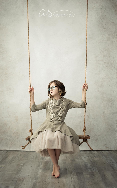 Beige tone photo of girl on swing