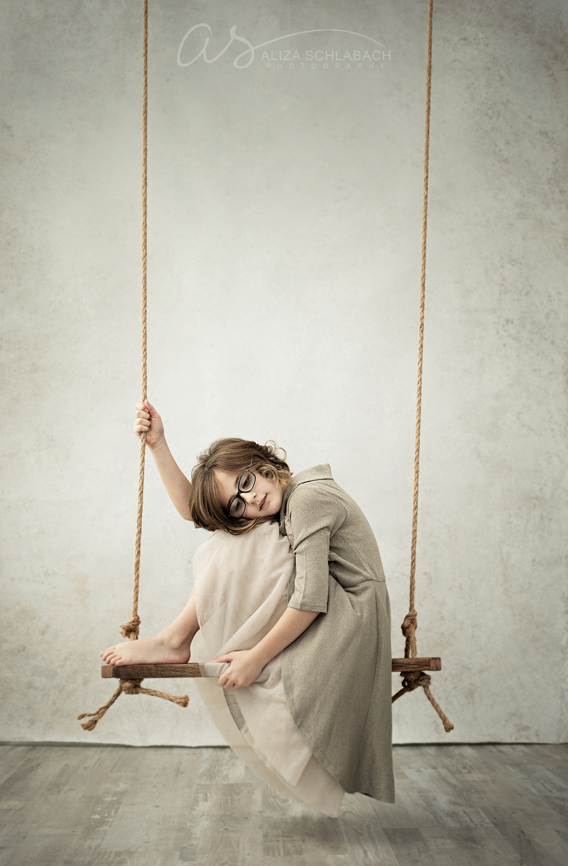 Fine art photo of a girl sitting sideways on a swing