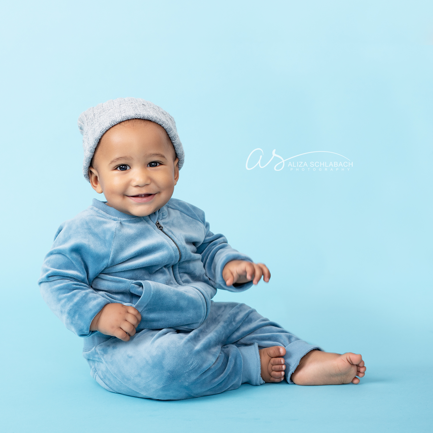 Adorable black baby sitting up in a blue track suit and hat