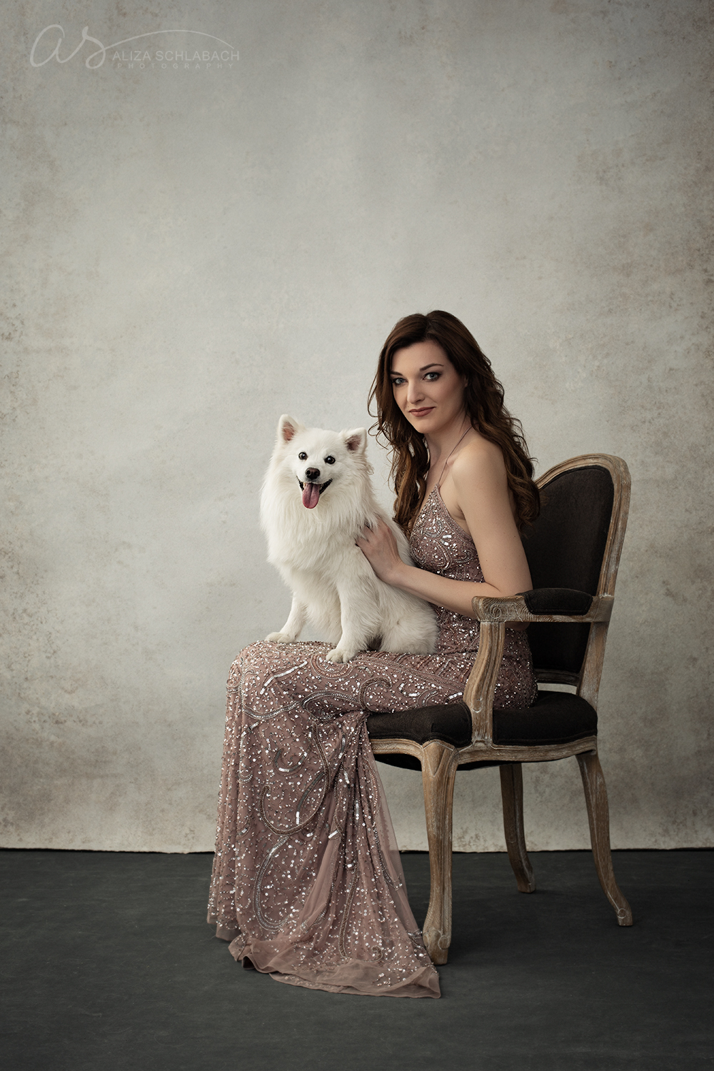 Pet photography - portrait of a glamorous woman in a sequin dress with her Miniature American Eskimo dog
