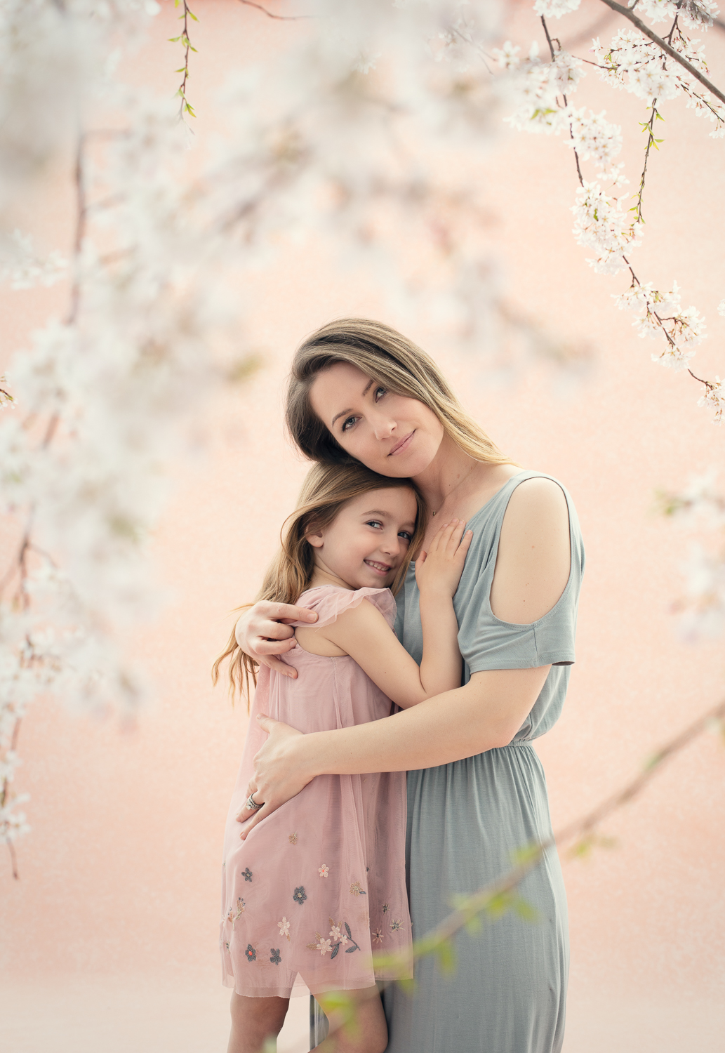 Portrait of a mother and daughter embracing | pink | cherry blossoms