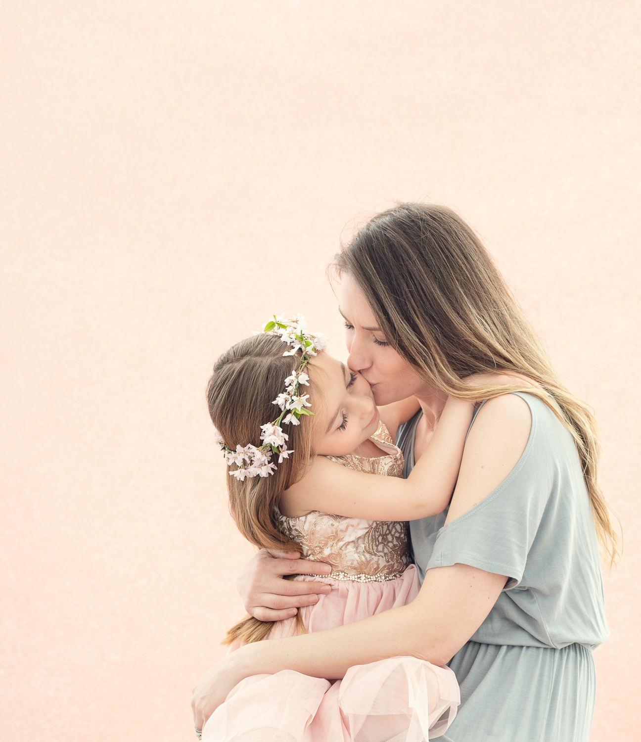 Portrait of a mother holding and kissing her young daughter on a pink backdrop