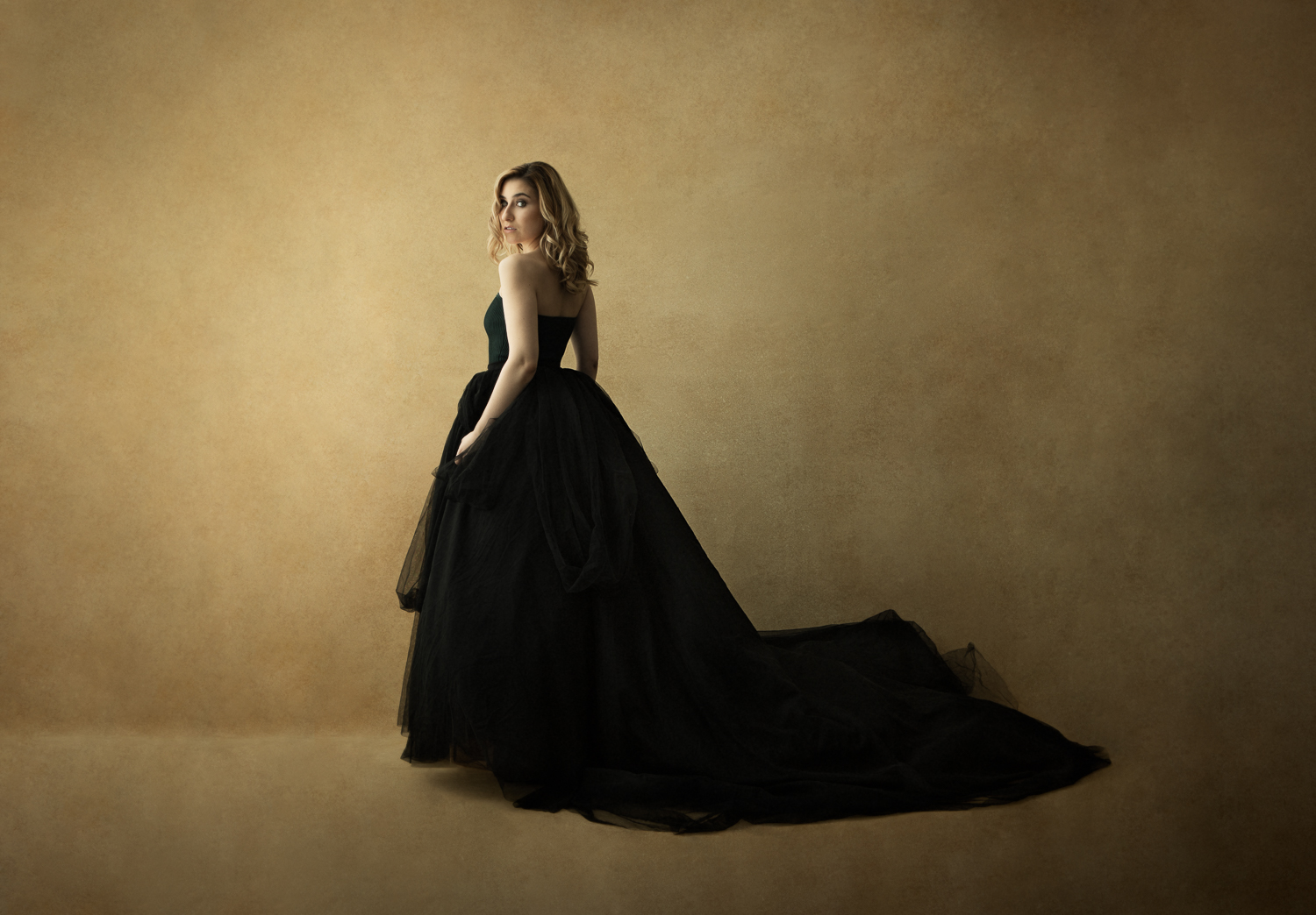 Vanity Fair style portrait of a young woman in a black gown on a gold canvas backdrop