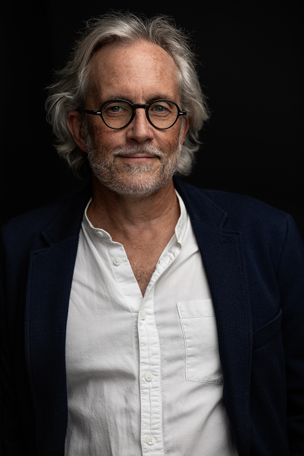 Headshot photo of a distinguished professor and author with silver hair and glasses