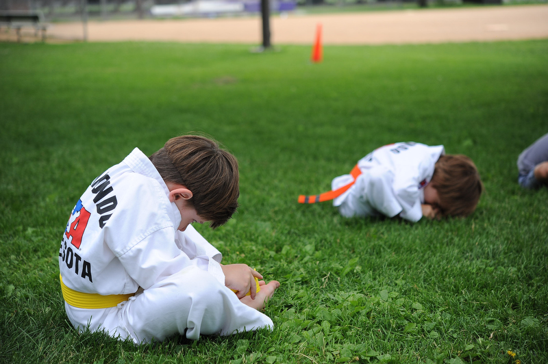 Harrison, her next door neighbor, practices his stretching... his personal challenge: to touch his nose to his toes!