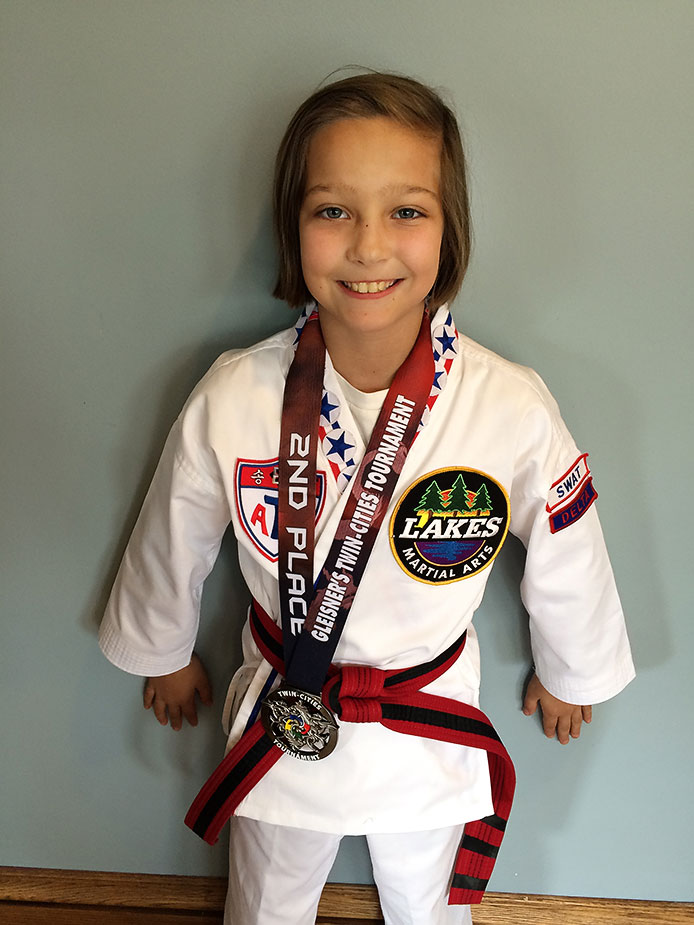 """This Lakes Martial Arts student stands proud with her second place medal in forms competition. Congrats on the hard work, Sylvi, especially at your first tournament!""""Internal rewards are those that affect you as a human. They often stay with you a long time. In some cases, this internal reward can affect your life forever,"""" says Grandmaster H.U. Lee."""
