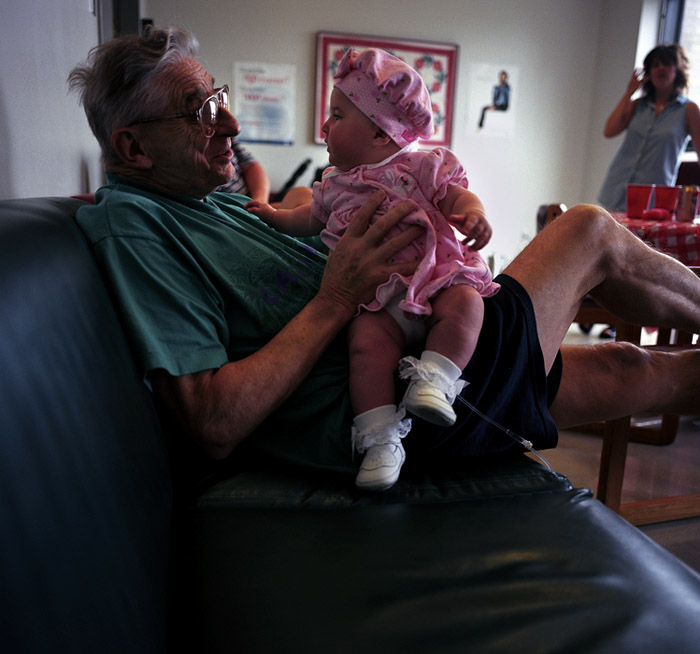 John, a retired Lieutenant in the New York Fire Dept. holds his first granddaughter in the commons room on the 8th floor of Mt. Sinai Hospital.