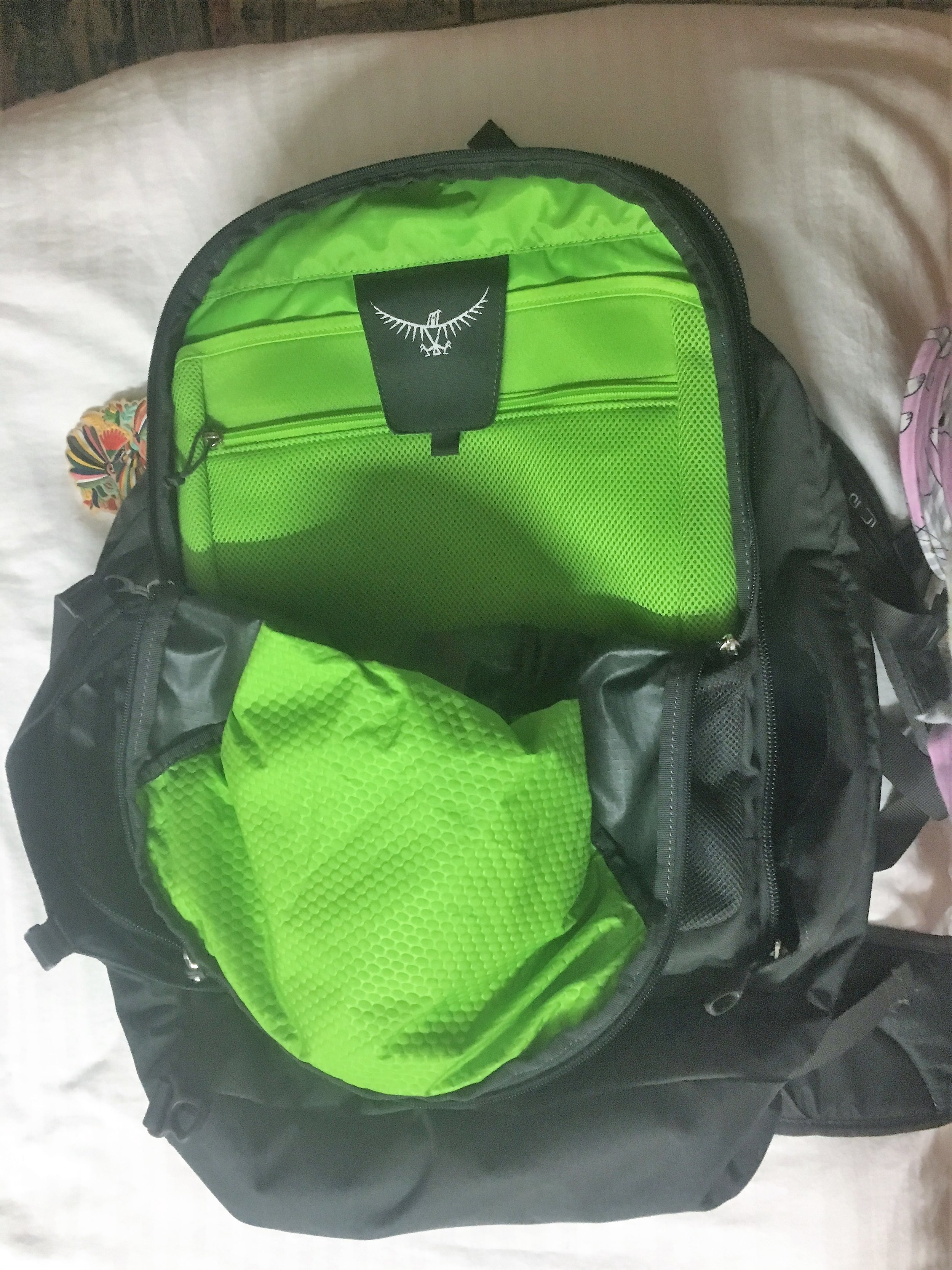 Bag unzipped showing the smaller front pocket with padded laptop sleeve at the back