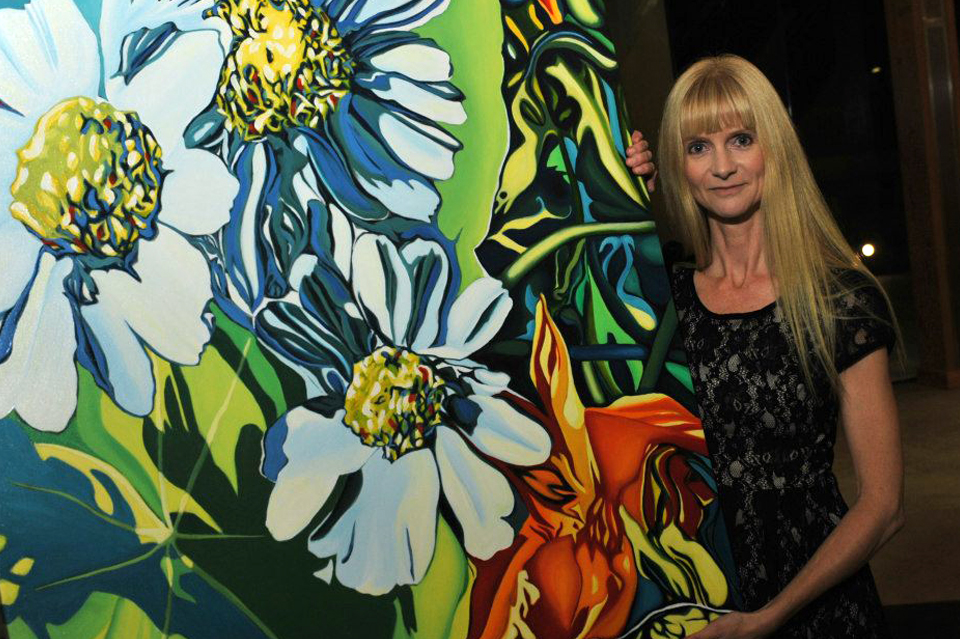 "Grant recipient Anne Gudrun stands next to her painting ""Daisies"" at the ""Tribute to the Arts"" event."