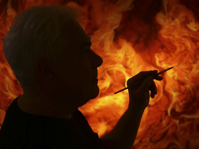 """Artist Carlo D'Alessio is silhouetted against his new painting titled """"Hot Stuff"""" as it hangs on the wall in his home studio in Palm Springs. The 48 x 72 inch painting uses acrylic and varnish on hard board and depicts fire. Photograph by Crystal Chatham,  The Desert Sun."""