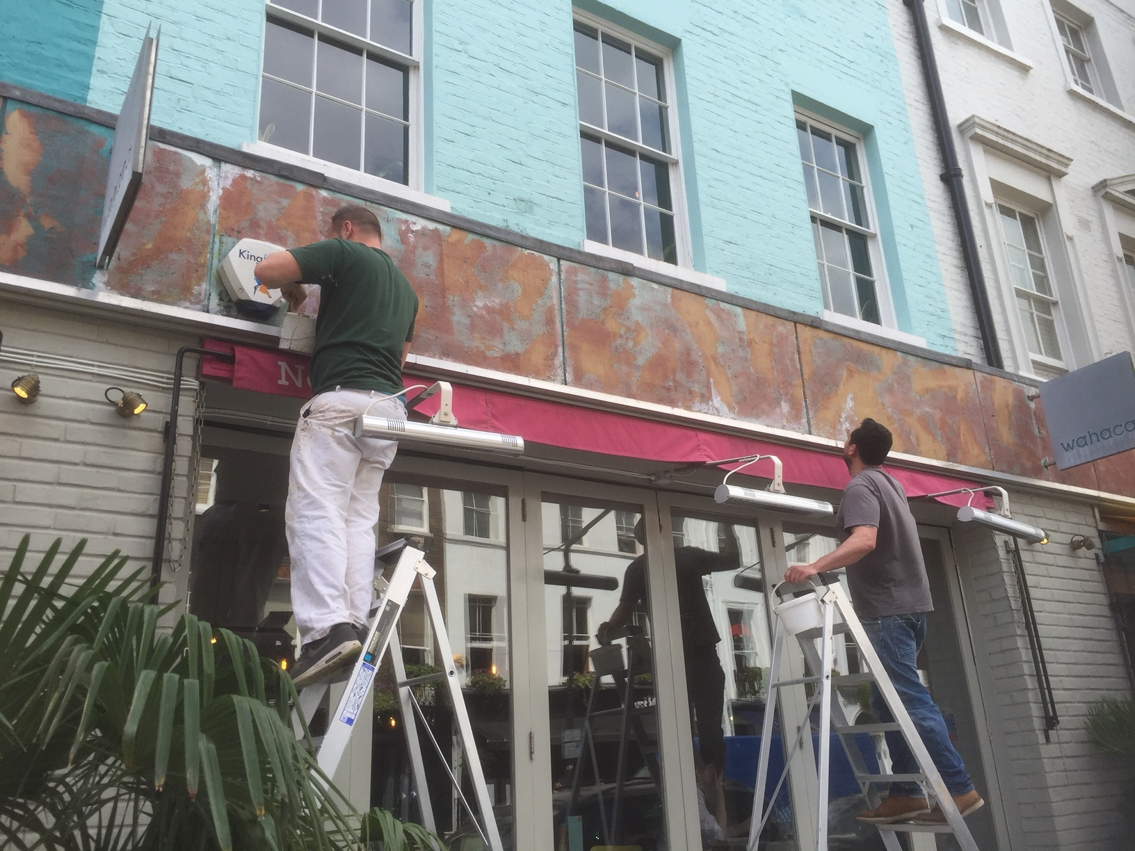 Getting to work on the Wahaca Restaurant sign, Charlotte Street in London.